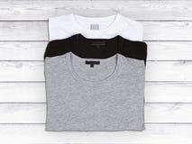 3 пустых футболки на белой деревянной предпосылке Стоковое фото RF