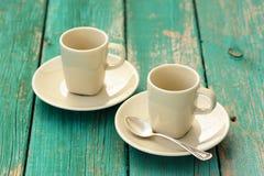 2 пустых чашки эспрессо чёрного дерева с серебряной ложкой на sha бирюзы Стоковые Изображения RF