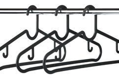3 пустых черных вешалки/вешалки одежд на рельсе одежд Стоковая Фотография RF