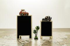 2 пустых черных доски с автомобилем на верхней части на карте мира с пальмой Стоковое фото RF