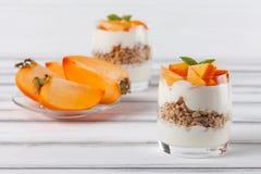 Пустяк хурмы сметанообразный в красивых стеклах, свежих зрелых кусках плодоовощ на белой деревянной предпосылке vegetarian еды зд Стоковые Фото