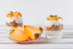 Пустяк хурмы сметанообразный в красивых стеклах, свежих зрелых кусках плодоовощ на белой деревянной предпосылке vegetarian еды зд Стоковые Изображения RF