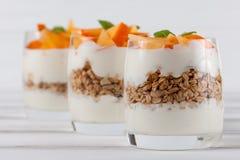 Пустяк хурмы сметанообразный в красивых стеклах, свежих зрелых кусках плодоовощ на белой деревянной предпосылке vegetarian еды зд Стоковая Фотография
