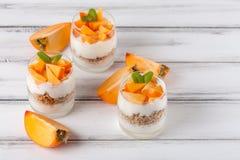 Пустяк хурмы сметанообразный в красивых стеклах, свежих зрелых кусках плодоовощ на белой деревянной предпосылке vegetarian еды зд Стоковые Изображения