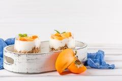 Пустяк хурмы сметанообразный в красивых стеклах, свежих зрелых кусках плодоовощ на белой деревянной предпосылке vegetarian еды зд Стоковое фото RF