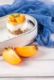 Пустяк хурмы сметанообразный в красивых стеклах, свежих зрелых кусках плодоовощ на белой деревянной предпосылке vegetarian еды зд Стоковое Фото