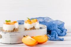 Пустяк хурмы сметанообразный в красивых стеклах, свежих зрелых кусках плодоовощ на белой деревянной предпосылке vegetarian еды зд Стоковое Изображение RF