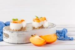 Пустяк хурмы сметанообразный в красивых стеклах, свежих зрелых кусках плодоовощ на белой деревянной предпосылке vegetarian еды зд Стоковые Фотографии RF