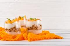 Пустяк хурмы сметанообразный в красивых стеклах, свежих зрелых кусках плодоовощ на белой деревянной предпосылке vegetarian еды зд Стоковое Изображение