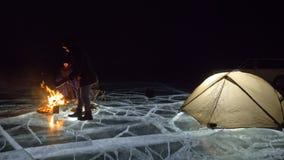 3 путешественника льдом огня право на на ноче Кемпинг на льде Шатер стоит рядом с огнем озеро baikal Рядом там видеоматериал