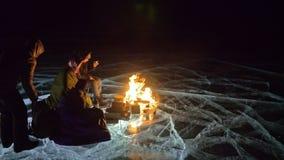 4 путешественника льдом огня право на на ноче Кемпинг на льде Шатер стоит рядом с огнем Люди греют вокруг акции видеоматериалы