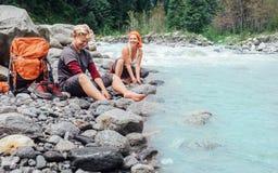2 путешественника освежая на береге реки горы Стоковое Изображение RF