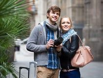 2 путешественника с цифровой фотокамера идя через улицу города Стоковые Фотографии RF