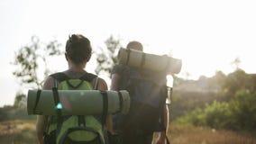 2 путешественника - человек и женщина с огромными рюкзаками пеший Идти холмами травы Блески Солнця на предпосылке видеоматериал