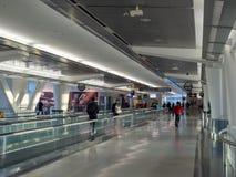 Путешественники идут к их стробу отклонения в авиапорте SFO стоковые фотографии rf