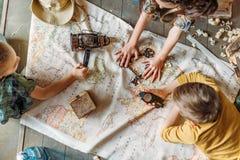 Путешественники маленьких ребеят сидя совместно на крылечке с картой Стоковая Фотография