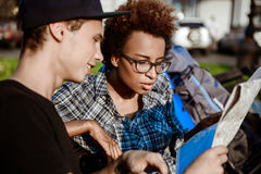 Путешественники наблюдая трассу на карте, сидя на стенде в парке Стоковые Изображения