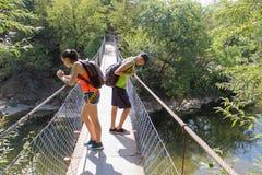 Путешественники путешествуют на висячем мосте идут trekking совместно Активные hikers Trekking совместно Туризм Eco и здоровое li Стоковое Изображение RF