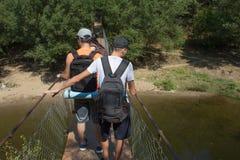 Путешественники путешествуют на висячем мосте идут trekking совместно Активные hikers Trekking совместно Туризм Eco и здоровое li Стоковые Фотографии RF