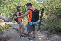 Путешественники путешествуют на висячем мосте идут trekking совместно Активные hikers Туризм Eco и здоровая концепция образа жизн Стоковое фото RF