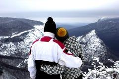 Путешественники смотрят красивый сценарный ландшафт снежных гор в зиме стоковые изображения rf