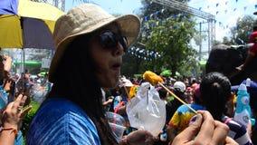 Путешественники тайских людей и иностранца играя и брызгая воду при женщины есть еду в фестивале Songkran