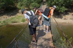 Путешественники, hikers на висячем мосте над рекой Стоковая Фотография