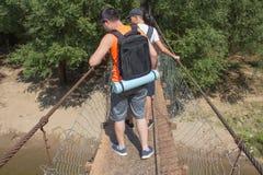 Путешественники, hikers на висячем мосте над рекой Стоковые Фото