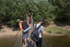 Путешественники, hikers на висячем мосте над рекой Стоковое Фото