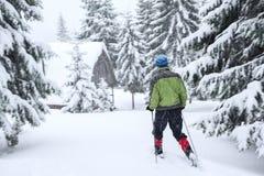 Путешественник в snowshoes идет к деревянной хате Стоковые Изображения RF