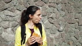 Путешественник девушки брюнета в куртке и рюкзаке есть плюшк-бургер на улице Быстрая закуска во время отключения Улыбки и взгляды сток-видео