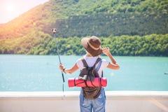 Путешественник девушки делает selfi с камерой действия на озере горы Она делает фото для блога перемещения Взгляд от задней части Стоковое Изображение RF