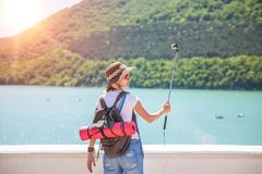 Путешественник девушки делает selfi с камерой действия на озере горы Она делает фото для блога перемещения Взгляд от задней части Стоковые Фотографии RF