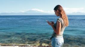 Путешественник девушки использует телефон и типы сообщение, океан и горы на предпосылке сток-видео