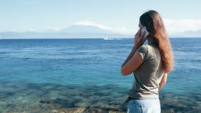 Путешественник девушки использует телефон, ответы вызывает, замедленное движение Океан, горы на предпосылке акции видеоматериалы