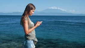 Путешественник девушки использует телефон, типы сообщение Океан, горы на предпосылке, замедленном движении видеоматериал
