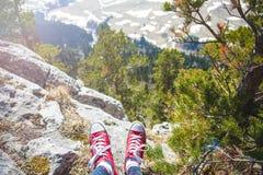 Путешественник девушки ноги который сидит на горе и смотрит взгляд плато горы от задней части туристского путешественника на пред Стоковая Фотография RF
