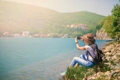 Путешественник девушки сидит на озере горы и фотографирует девушка принимает фото для блога перемещения Взгляд от задней части ту Стоковая Фотография