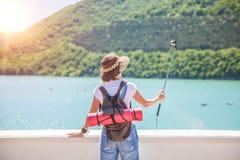 Путешественник девушки с камерой действия на девушке озера горы принимает фото для взгляда блога перемещения от задней части тури Стоковое Фото