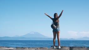 Путешественник девушки с рюкзаком распространяет ее оружия широкие, наслаждается взглядом океана, вулкана сток-видео