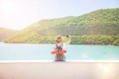 Путешественник девушки с smartphone на девушке озера горы принимает фото для взгляда блога перемещения от задней части туристског Стоковые Фотографии RF