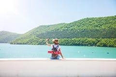 Путешественник девушки с smartphone на девушке озера горы принимает фото для взгляда блога перемещения от задней части туристског Стоковое Фото