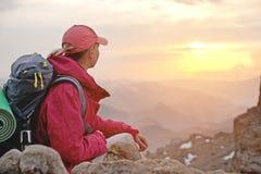 Путешественник девушки конца-вверх a сидит на утесе высоко в горах Кавказа против фона заходящего солнца  Стоковое Изображение RF