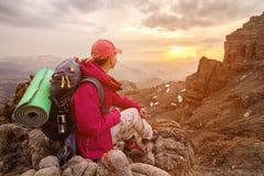 Путешественник девушки сидит на утесе высоко в горах Кавказа против фона заходящего солнца утесов и Стоковое Изображение