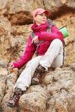 Путешественник девушки сидит на утесе высоко в горах Кавказа против фона заходящего солнца утесов и Стоковая Фотография RF