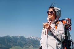 Путешественник женщины выпивает чай на верхней части горы Стоковое фото RF