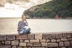 Путешественник женщины делая передвижное фото живописного ландшафта во время праздников перемещения сидя на старой стене во время Стоковое фото RF