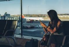 Путешественник женщины используя мобильный телефон пока сидящ в аэропорте ждать ее полет стоковая фотография rf