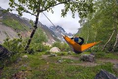 Путешественник женщины ослабляя в гамаке в горах Стоковая Фотография