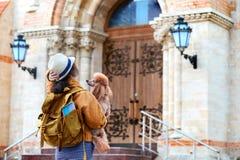 Путешественник женщины при рюкзак держа собаку рассматривает архитектурноакустический памятник стоковая фотография rf